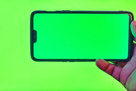 Mans hand shows mobile smartphone with green screen isolated on green background. Mock up mobile