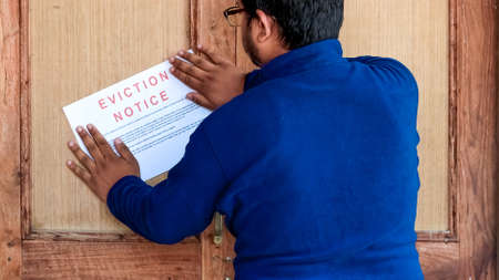 Man sticking eviction notice on the door of the tenant