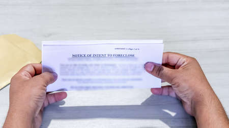 Hands of an Asian man holds Foreclosure Notice.