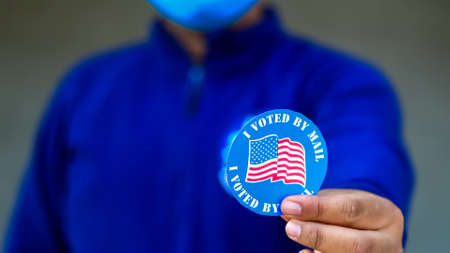 Man in mask from minority group produly holds Voted By Mail sticker during US Election closeup.