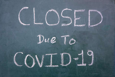 Closed Due To Coronavirus text infront of a cafe shop. Impact of coronavirus on business. Stock Photo