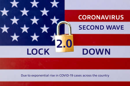 Concept Of Second Lockdown in US. Real padlock placed on top of the American flag to indicate second national lockdown in US due to rise in COVID-19 cases.