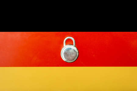 Concept Of Second Lockdown in Germany. Real padlock placed on top of the German flag to indicate second national lockdown in the country due to rise in COVID-19 cases. Stock Photo