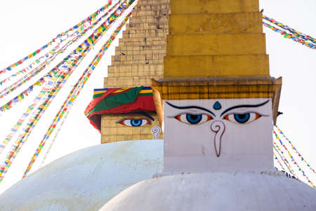 Kathmandu, Nepal - January 29 2021: Buddhist Manuscripts inscribed on the golden bell with Boudhanath Stupa in the background.
