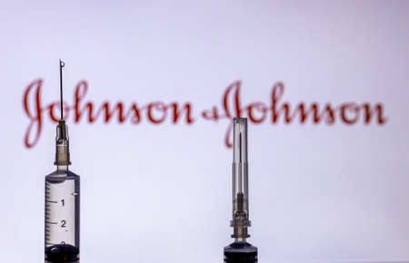 Kathmandu, Nepal - February 7 2021: Syringe Injection placed against Johnson and Johnson logo. JnJ coronavirus vaccine will work with only 1 dose as compared to two doses required by other vaccines.