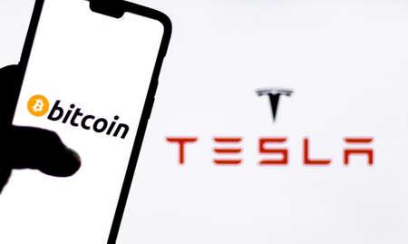 Kathmandu, Nepal - February 8 2021: Bitcoin logo on a smartphone against Tesla logo in the background.