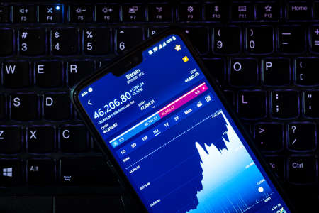 Kathmandu, Nepal - February 8 2021: Stock value of Bitcoin on a smartphone against laptop keyboard. Bitcoin has spiked to the highest value yet after Tesla invested $1.5 Billion. Publikacyjne