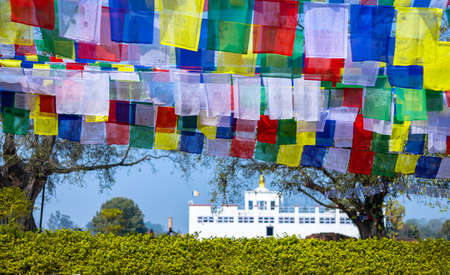 Many prayer flags in the wind against the Holy Maya Devi Temple in Lumbini, Nepal.
