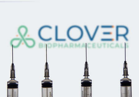 Kathmandu, Nepal - March 17 2021: Four syringe or injection needles against Clover Biopharmaceuticals logo in the background. Vaccine Concept.