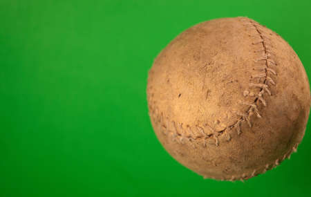 A close up of a old softball with a green screen. photo