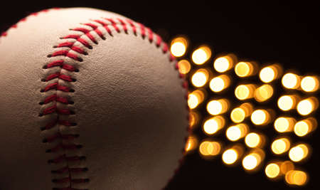 A close up of a new baseball at night with stadium lights in the back ground.