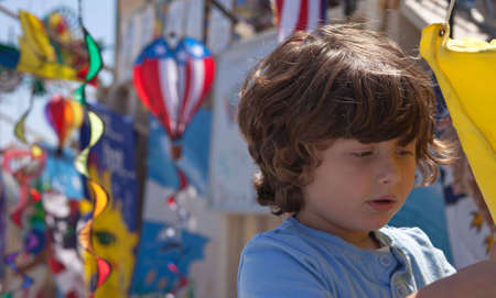 A close up of a young boy looking at wind spinners. Stock Photo - 5106634
