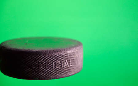 A close up of a old ice hockey puck with a green screen. Stock Photo