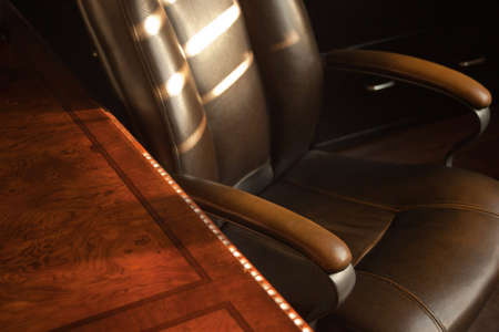 A close up of a old leather office chair and wood desk during sunset. Stok Fotoğraf