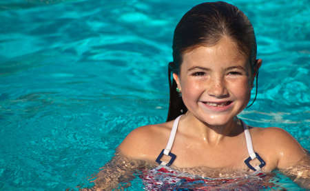 A close up of a young girl on a summer day in the pool. photo