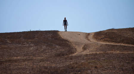 A shot of a woman reaching the top of a hill after a long walk. photo