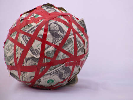 A shot of a ball of a bunch of dollar bills tied up in red tape.