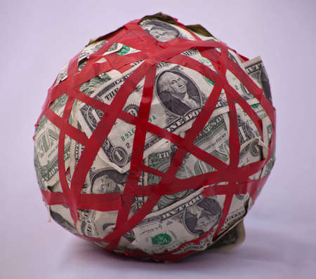 corporate waste: A shot of a ball of a bunch of dollar bills tied up in red tape.