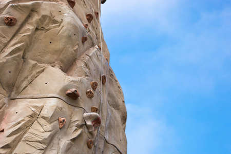 A shot of a climbing wall with a blue sky. Stock Photo