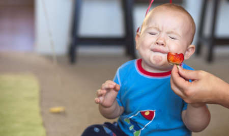 A shot of a young baby boy just taking a bite of a sour strawberry. Stock Photo