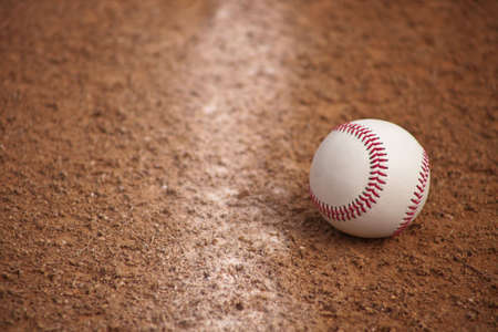dirt: A close up of a baseball stopping just inside fair territory.