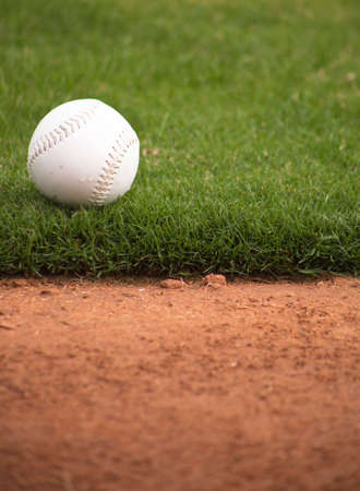 A close up of a softball sitting just off the infield dirt. Stock Photo - 5790797