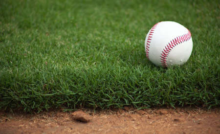 A close up of a baseball sitting just off the infield dirt. Stock Photo