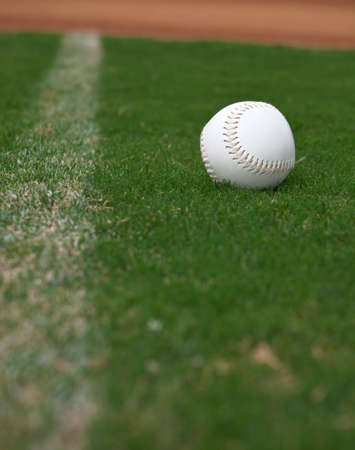 A close up of a softball sitting just inside the right field foul line. Stock Photo - 5790794
