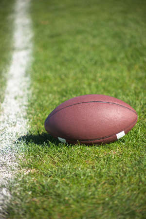 A close up of a American football on grass.
