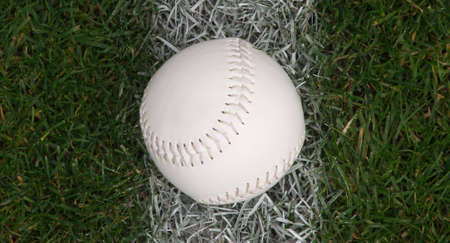 A close up of a softball sitting on the foul line.