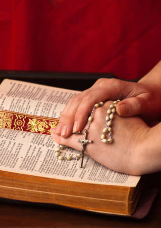 A close up of a young womans hands on the bible with rosary. Stock Photo