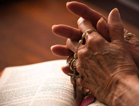 A close up of a senior womans hands on the bible with rosary. Stock Photo