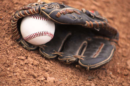 dirt: A close up of a baseball and glove sitting on dirt.