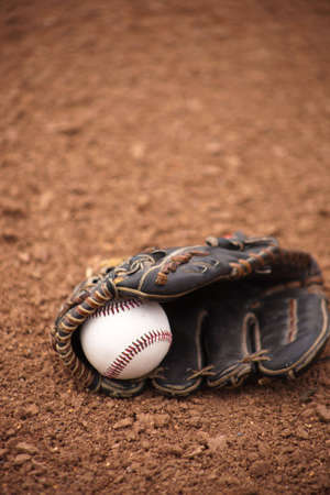 A close up of a baseball and glove sitting on dirt.