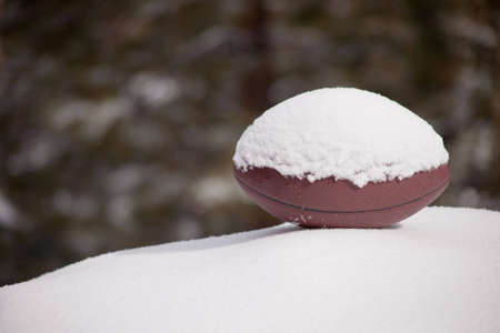 A close up of a football sitting on a snow hill with a green background.