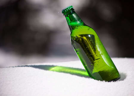 sapid: A close up of a green beer bottle sitting in snow. Stock Photo