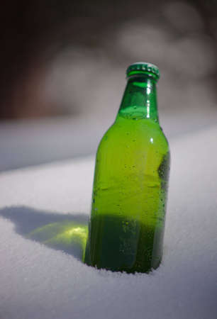 A close up of a green beer bottle sitting in snow. Stock Photo