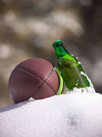 luxuriate: A close up of a football and green bottle of beer sitting in snow.