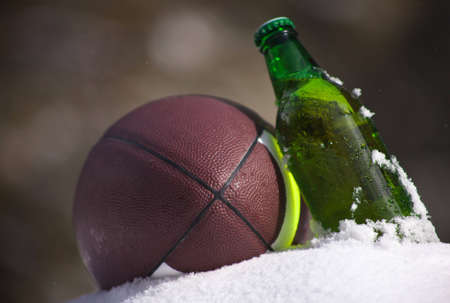 A close up of a football and green bottle of beer sitting in snow. photo