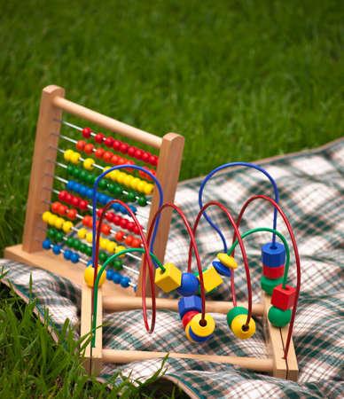 緑の芝生の上の格子縞の毛布の上に座って赤ちゃんのおもちゃのいくつかの。
