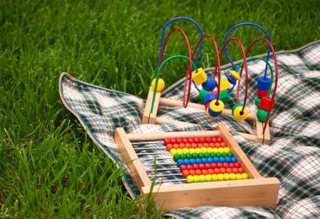 A 緑の草の格子縞の毛布の上に座って赤ちゃんのおもちゃのいくつかのクローズ アップ。