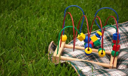 A 緑の草の格子縞の毛布の上に座って赤ちゃんグッズのクローズ アップ。 写真素材