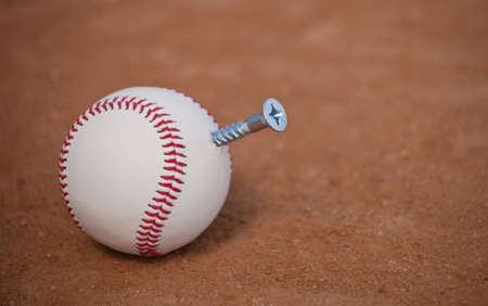 A close up of a baseball with a screw sticking out of it, symbolizing the baseball pitch the screwball. Stock Photo