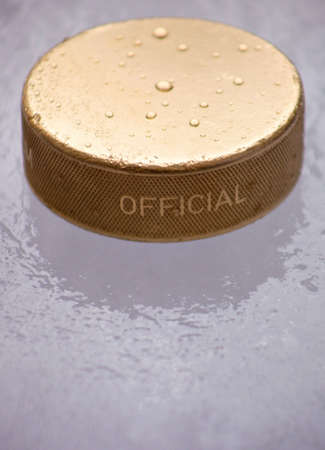 A close up of a gold ice hockey puck sitting on the ice. Stock Photo