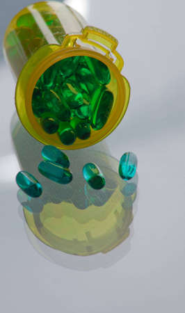 A close up of a bunch of turquoise pills wtih a yellow vial and a white glass background. photo