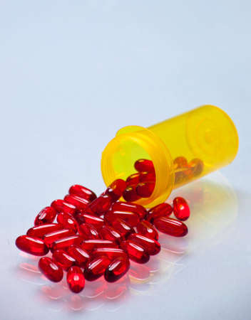 A close up of a bunch of red pills coming out of a yellow bottle with a white glass background. photo