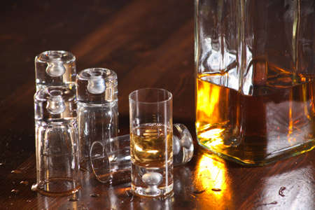 A close up of a bunch of  shot glasses and a bottle of whiskey on a old wood table. photo
