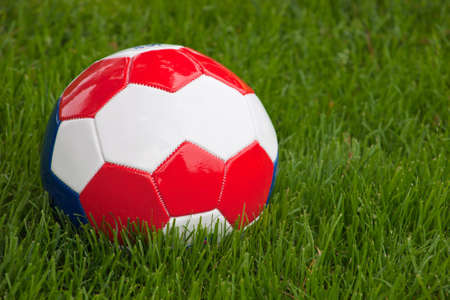 A close up of a red, white and blue soccer ball sitting in green grass. photo