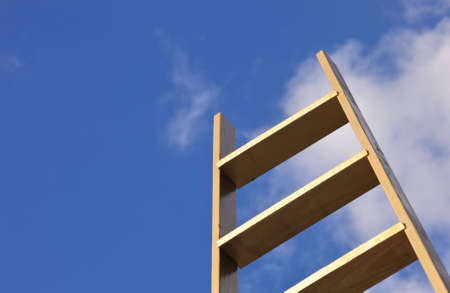 A close up of a gold ladder sticking up into a blue sky. photo