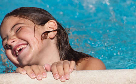 A close up of a young girl laughing poolside.